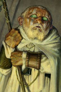 A small man in robes with a white beard and green eyes stares warily.