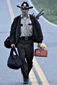 Andrew Lincoln as Deputy Rick Grimes walks down the road carrying a lot of weapons and a gas can.